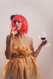 Attractive model woman taste red wine with fingers. Attractive model woman in red wig taste red wine with fingers Stock Images