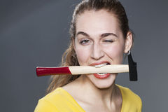 Attractive modern girl biting hammer and winking for fun DIY Royalty Free Stock Photo