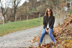 Attractive modern woman sitting in a autumn park royalty free stock photo