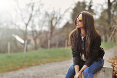 Attractive modern woman sitting in a autumn park royalty free stock images