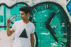 Attractive modern young brazilian guy in front of graffiti wall royalty free stock photo