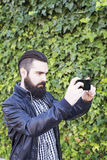 Attractive, modern young man with beard takes a picture with your smartphone. stock images