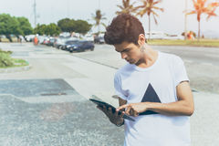 Attractive modern young white male using tablet near sea promenade. Attractive modern young white male with black hair in white t-shirt using tablet, standing on Stock Photography