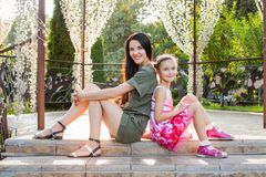 Attractive mom and daughter sitting on stairs in beautiful park. Attractive mom and daughter sitting together on stairs in arbour in beautiful park, they smiling Stock Photo