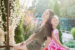 Mom and little daughter sitting in arbour in nature Royalty Free Stock Images