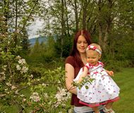 Attractive Mom and Toddler Looking at Apple Tree. This young mother and toddler daughter are looking at an apple tree in bloom Stock Images