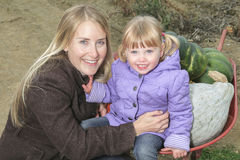Attractive Mother and Daughter Portrait in Pumpkin royalty free stock photography