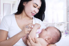 Attractive mother feeding her baby at home Royalty Free Stock Image