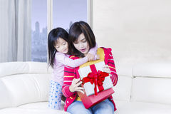 Attractive mother and girl open a gift on sofa royalty free stock photos