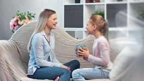 Attractive mother giving gift box cute teenage daughter celebrating holiday having positive emotion. Medium shot. Astonished smiling little girl laughing stock video