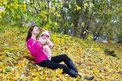 Attractive mother holding a baby girl playing with falling autumn leaves. Attractive young mother holding a baby girl playing with falling autumn leaves Royalty Free Stock Photo