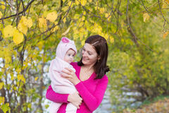 Attractive mother holding a baby girl playing with falling autumn leaves. Attractive young mother holding a baby girl playing with falling autumn leaves Royalty Free Stock Image