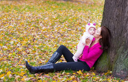 Attractive mother holding a baby girl playing with falling autumn leaves. Attractive young mother holding a baby girl playing with falling autumn leaves Stock Photo