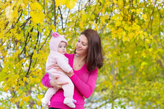 Attractive mother holding a baby girl playing with falling autumn leaves Royalty Free Stock Photo