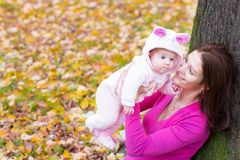 Attractive mother holding a baby girl playing with falling autumn leaves. Attractive young mother holding a baby girl playing with falling autumn leaves Royalty Free Stock Photos