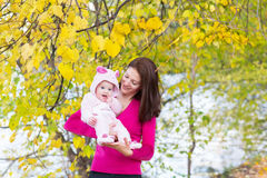 Attractive mother holding a baby girl playing with falling autumn leaves Stock Photography