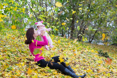 Attractive mother holding a baby girl playing with falling autumn leaves Stock Image