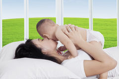 Attractive mother kissing her child on bed Stock Images