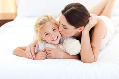 Attractive mother kissing her little girl Stock Photo