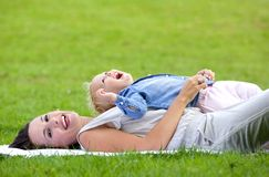 Attractive mother lying down on grass with daughter. Portrait of an attractive mother lying down on grass with daughter royalty free stock photos
