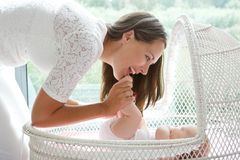 Attractive mother playing with baby in cot Royalty Free Stock Photo