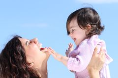 Attractive mother raising her daughter and playing together Stock Images