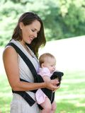 Attractive mother smiling with baby in sling Stock Photo