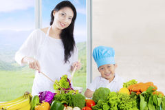 Attractive mother and son make salad. Portrait of attractive young mother and her son make salad for lunch with table full of vegetables Stock Photos