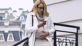 Attractive mother-to-be having contractions calling 911 ambulance on smartphone. Stock footage stock footage