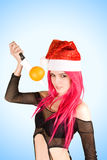 Attractive mrs. Santa with orange on the knife royalty free stock image