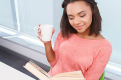 Attractive mulatto lady drinking tea and reading Royalty Free Stock Image