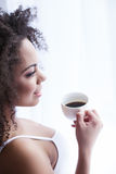 Attractive mulatto woman is enjoying hot beverage royalty free stock photos