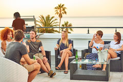 Attractive multi-ethnic group of friends socialising at a rooftop barbecue. Attractive group of young people socialising on a rooftop with a view of the ocean Royalty Free Stock Photos