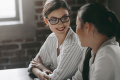 Attractive multicultural businesswomen talking while sitting in modern office. Two attractive multicultural businesswomen talking while sitting in modern office royalty free stock photo