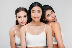 Attractive multicultural girls in white bras posing together. Isolated on grey royalty free stock photo