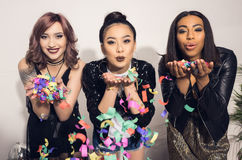 Attractive multiethnic girls blowing confetti at party Royalty Free Stock Photo