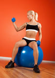 Attractive muscular blonde sitting on fitness ball. Beautiful blond athlete sitting on fitness ball and doing exercise on biceps Stock Photo