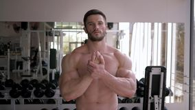 Muscular bodybuilder bare-chested with athletic body before mirror and does warm-up before power workout at sports. Attractive muscular bodybuilder bare-chested stock video footage