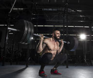 Attractive muscular bodybuilder doing heavy squat exercise in mo. Attractive muscular shirtless bodybuilder doing heavy squat exercise in modern fitness center stock photo