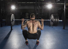 Attractive muscular bodybuilder doing heavy squat exercise in mo. Attractive muscular shirtless bodybuilder doing heavy squat exercise in modern fitness center stock image