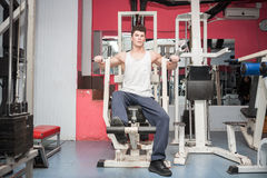 Attractive muscular guy exercising in the gym Stock Photos