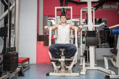 Attractive muscular guy exercising in the gym Royalty Free Stock Photography
