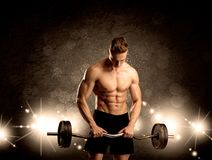 Strong sexy male working out. An attractive muscular guy working out with weights and showing naked upper body with illustrated lights and bokeh concept Royalty Free Stock Photography