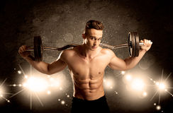 Strong sexy male working out. An attractive muscular guy working out with weights and showing naked upper body with illustrated lights and bokeh concept Royalty Free Stock Photo