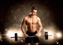 Strong sexy male working out. An attractive muscular guy working out with weights and showing naked upper body with illustrated lights and bokeh concept Stock Images