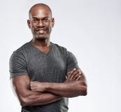 Attractive muscular happy man with folded arms. Single handsome grinning confident young Black adult with shaved head and folded muscular arms over gray Royalty Free Stock Photography