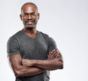 Attractive muscular happy man with folded arms. Single handsome grinning confident young Black adult with shaved head and folded muscular arms over gray Stock Image
