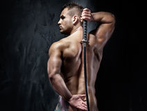 Attractive muscular man posing with sword. Young handsome naked man posing with samurai sword Stock Photography