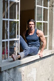 Attractive, muscular man sitting on open window Royalty Free Stock Photo