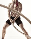 Attractive muscular man working out with heavy ropes. Royalty Free Stock Photos